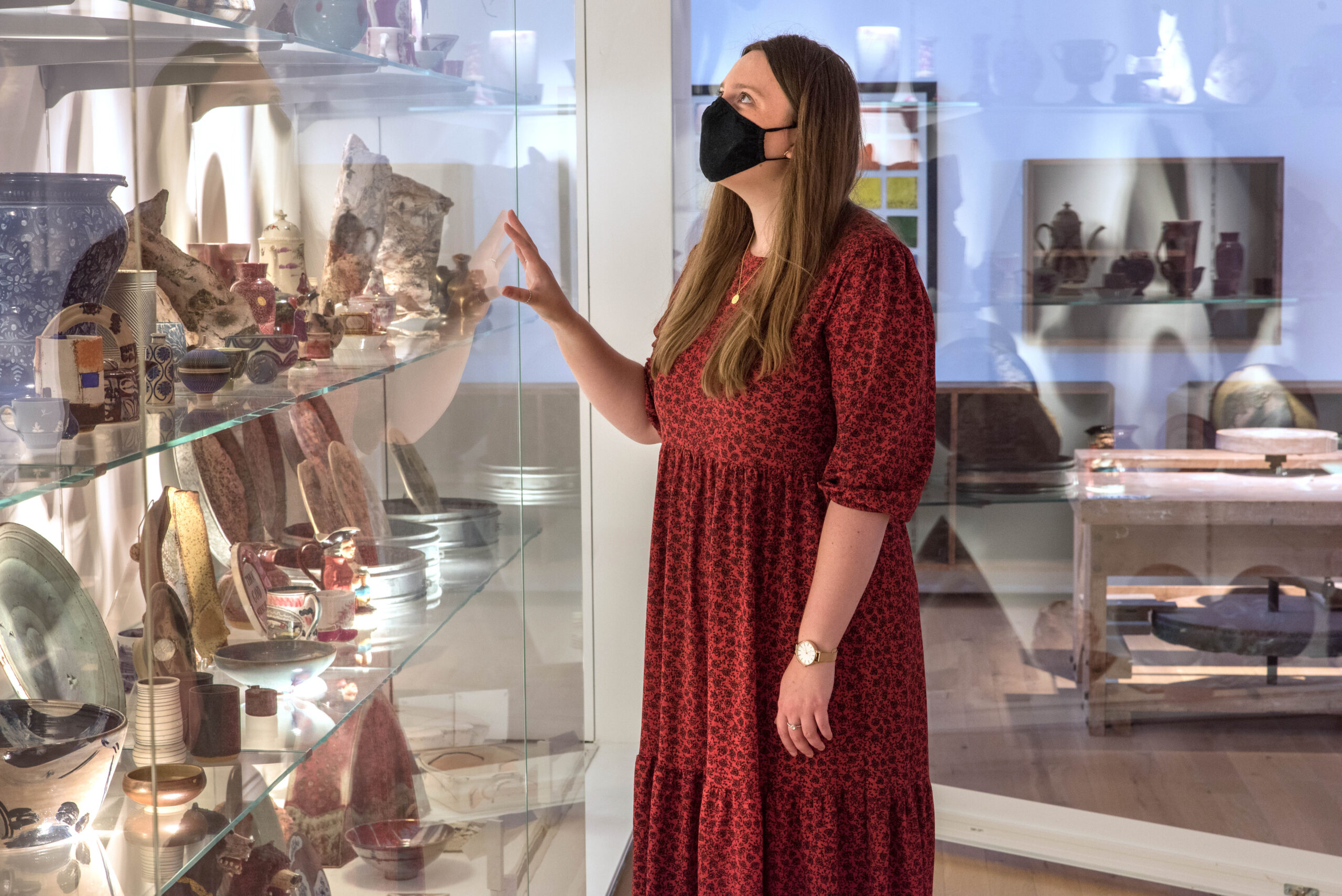 Woman in a red dress and black masks stands in front of a glass case filled with ceramics