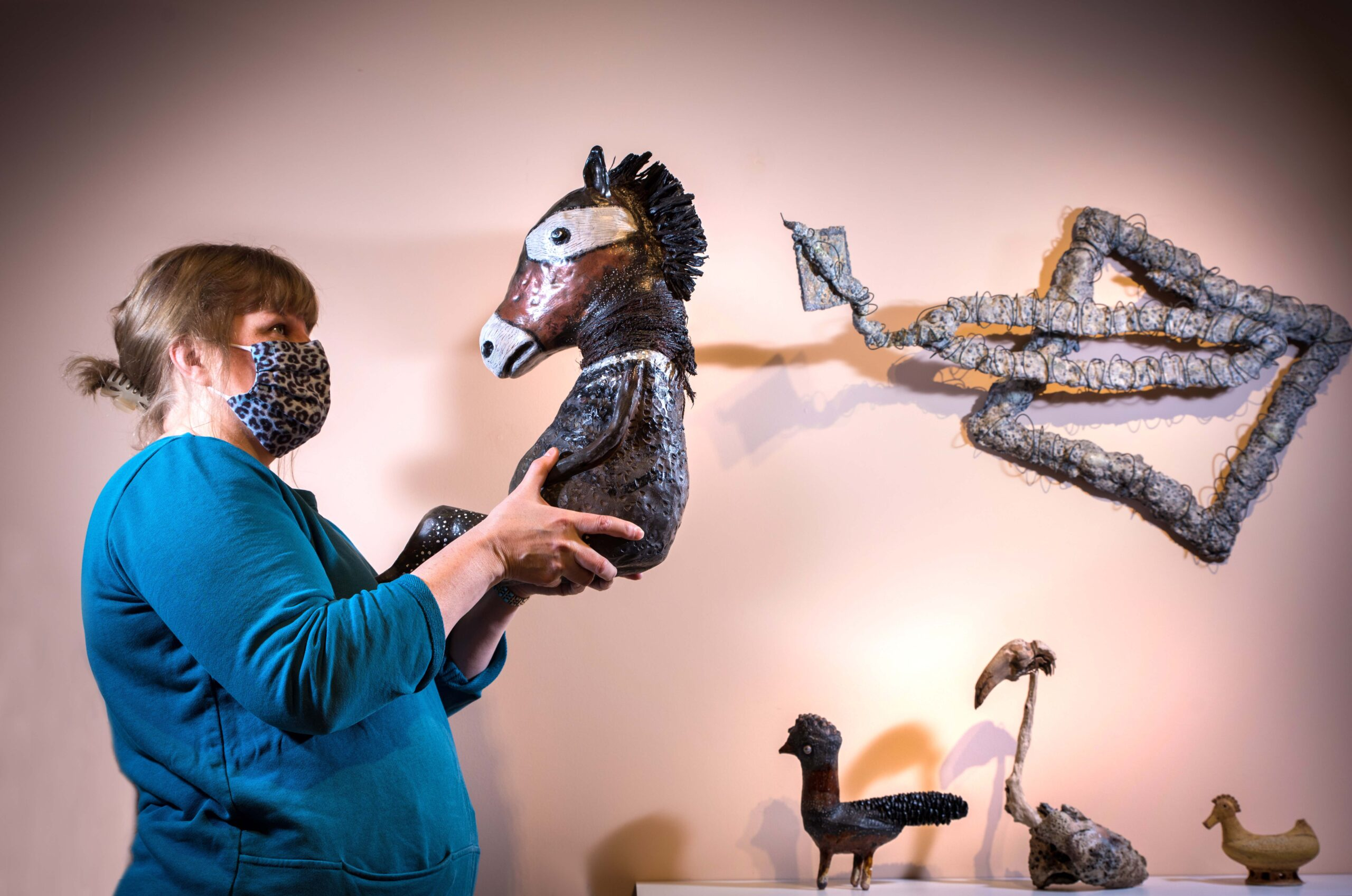 Curator holds an artwork shaped like a horses head. On the right parts of other sculptures can be seen on the wall and bird shaped sculptures on the bottom right