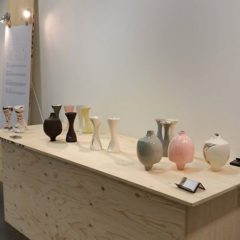 A wooden bench with small ceramic vases in different colours