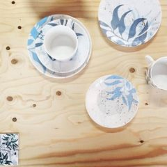 Teacups and saucers with a white and blue pattern on a wooden surface