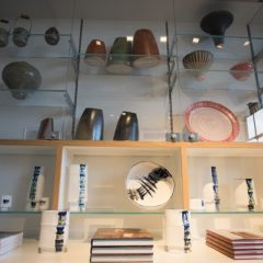 Wooden shelves with ceramic plates, vases and books on