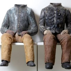 Two headless ceramic sculptures of seated men on a shelf