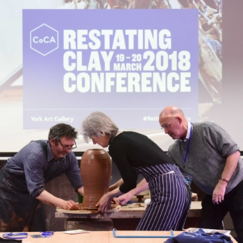Three artists moving a piece of pottery. The pottery is in front of a projector screen.