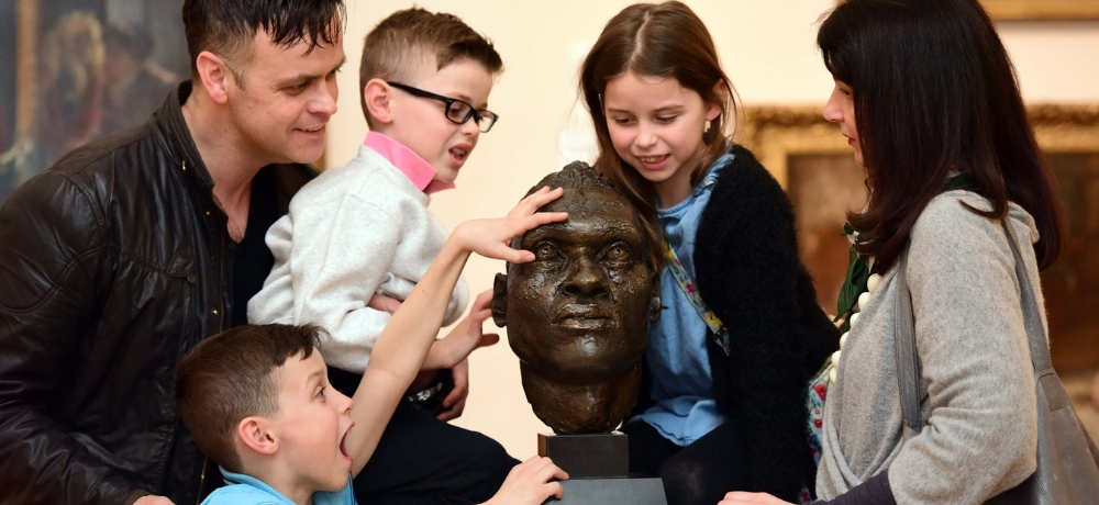 A family admiring a head sculpture.