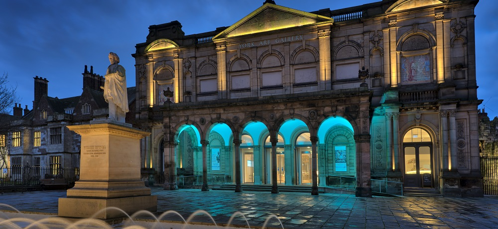 York Art Gallery at night. The entrance has been illuminated blue.